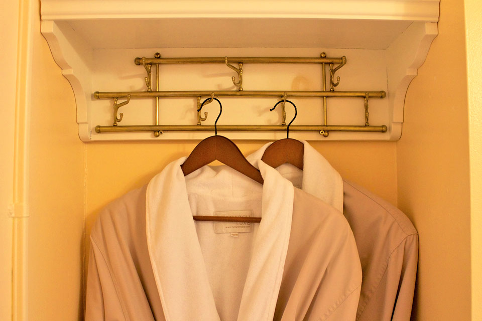 Soft bathrobes hanging from antique brass wall hooks in bathroom of Room 6 at WsInn in Burlington, VT.