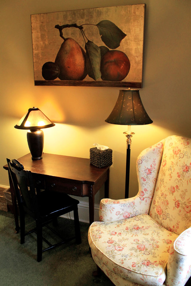 Writing desk and yellow wingback armchair in the cobblestones room.