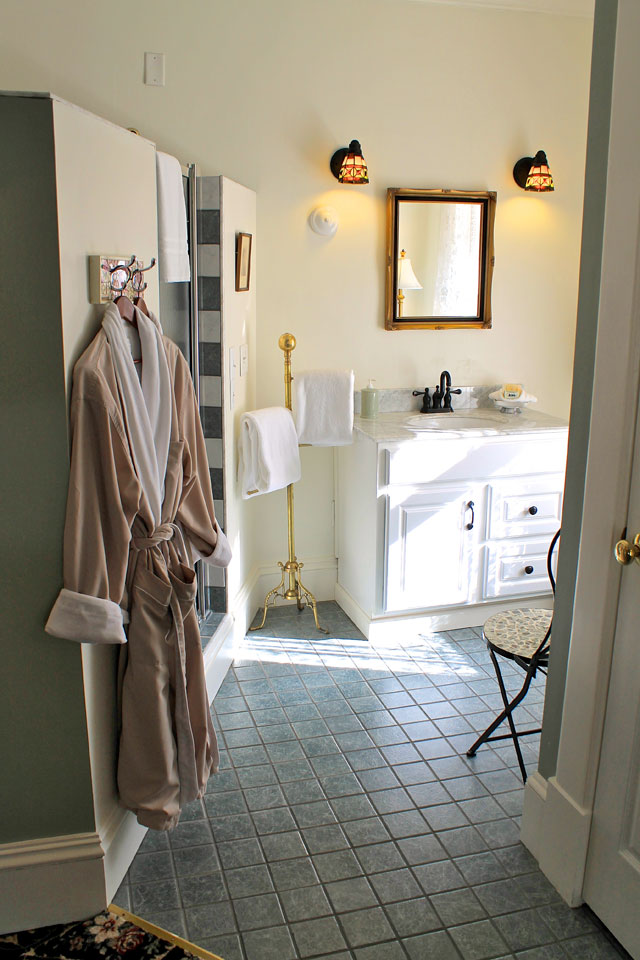 Soft Bathrobes hang just outside the two-person tiled shower of the Woodhouse Suite.