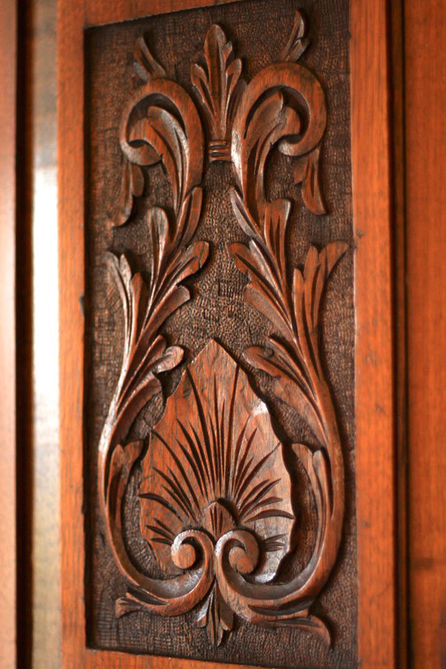 Close-up of elaborate wooden carvings on the front of antique wardrobe in Room 8 of WSInn in Vermont.