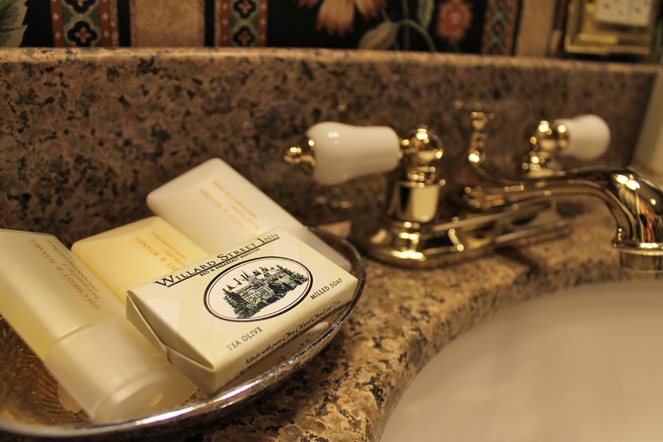 Close-up of the granite vanity top with modern bath amenities at the Willard St Inn.