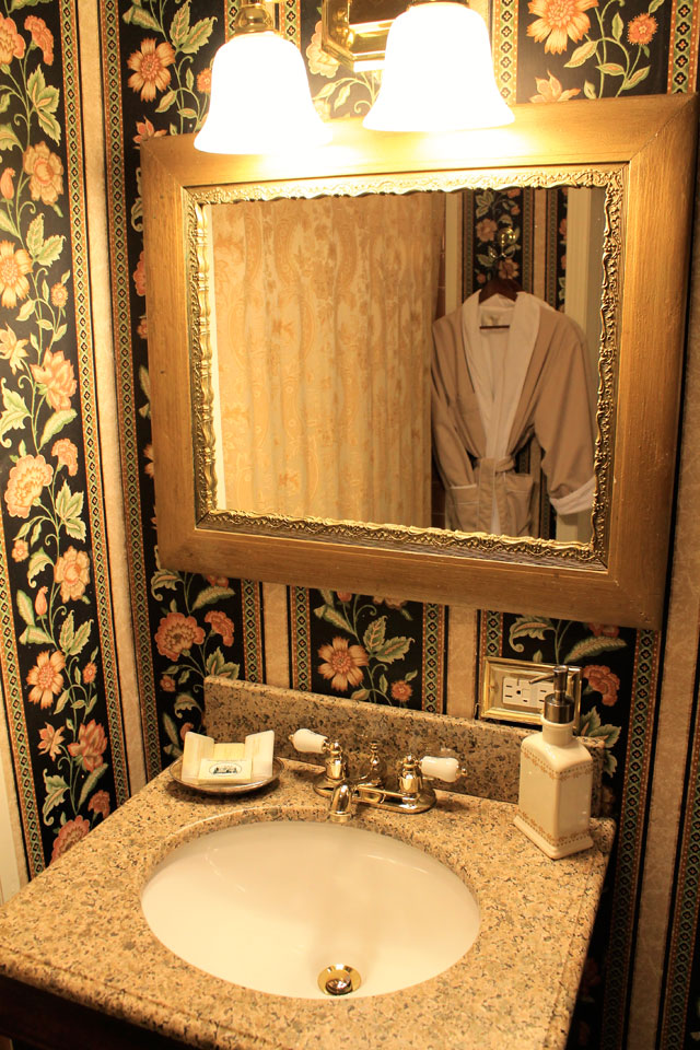 Granite vanity top with antique mirror in private bath of Rm 14.