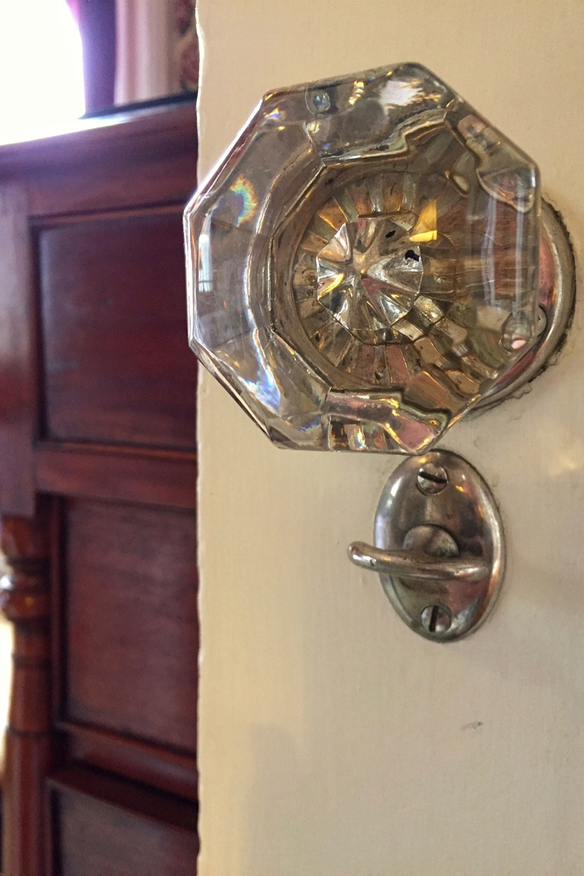Close-up of antique glass doorknob of bathroom door in Victorian Cabernet at WSInn.