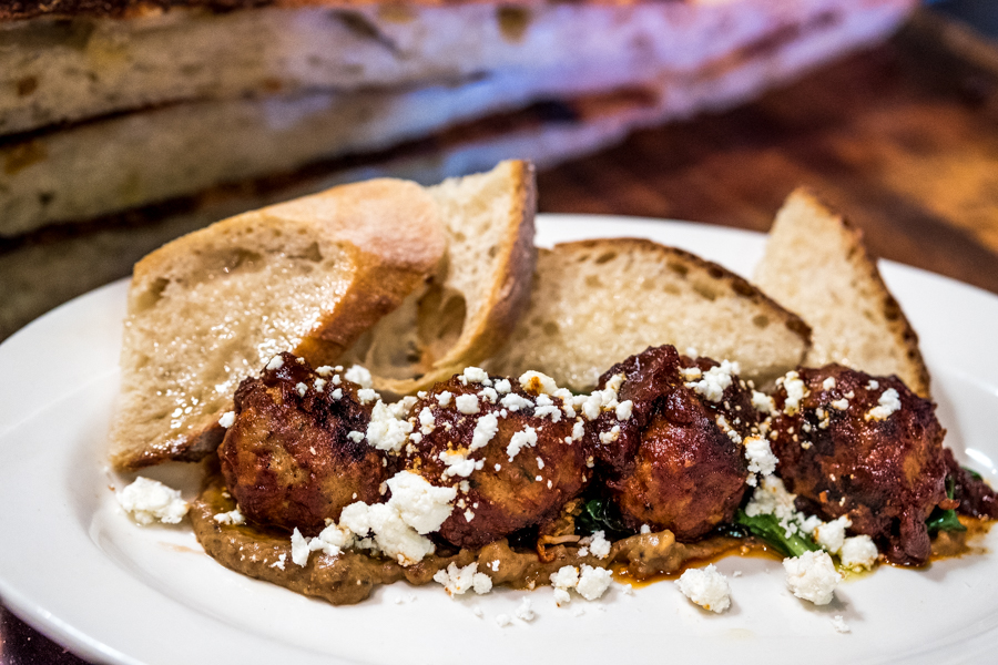 M'tucci's Italian Market & Pizzeria Meatball appetizer: meatballs with tomato agridulce, sautéed spinach, feta, apple chutney and toasted bread.