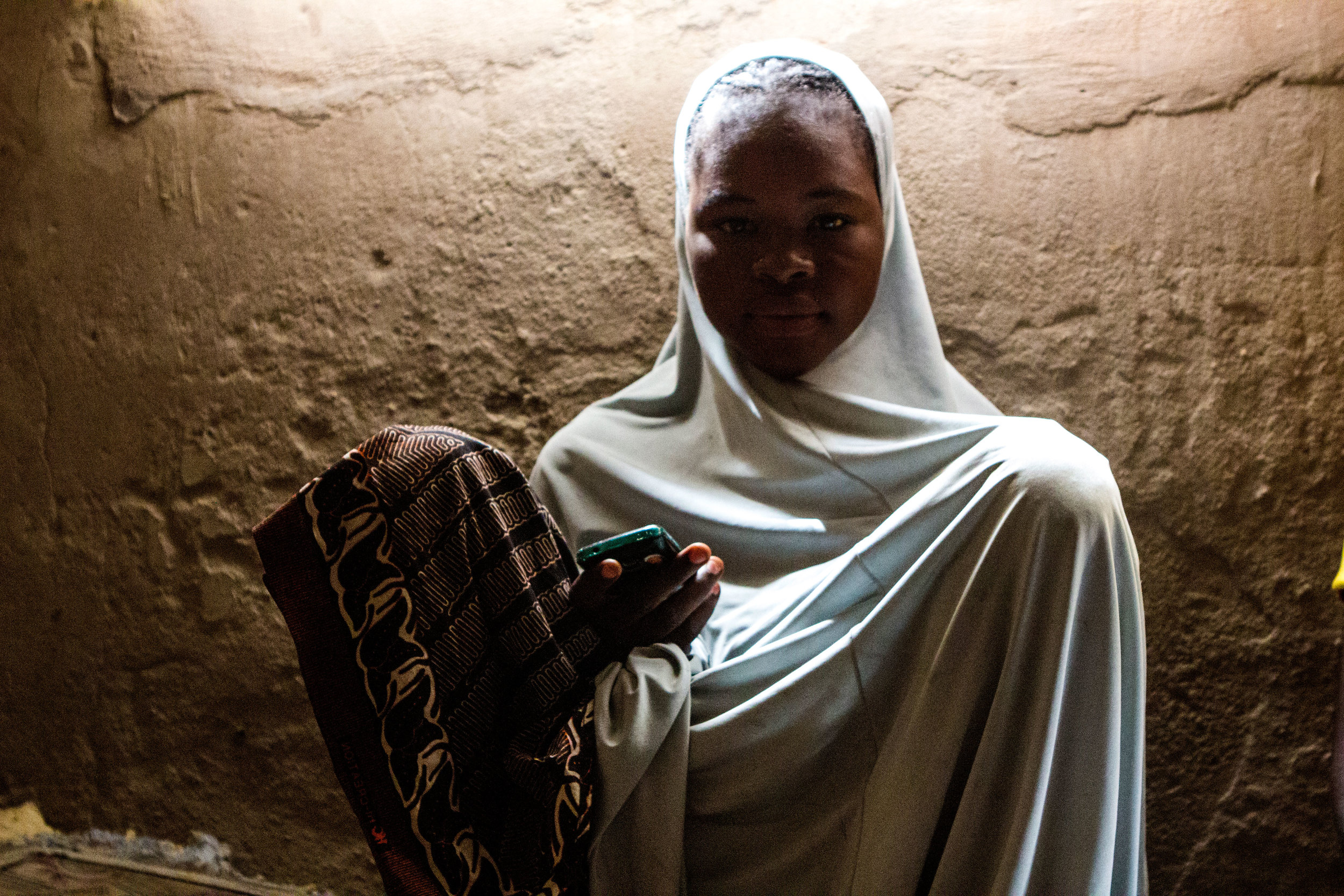 Yola, Nigeria. March 6 2015. Aisha, 17, poses for a photo after sending SMS messages on her cell phone. She sits in the one-room house her family now rents after fleeing Boko Haram violence in her hometown.