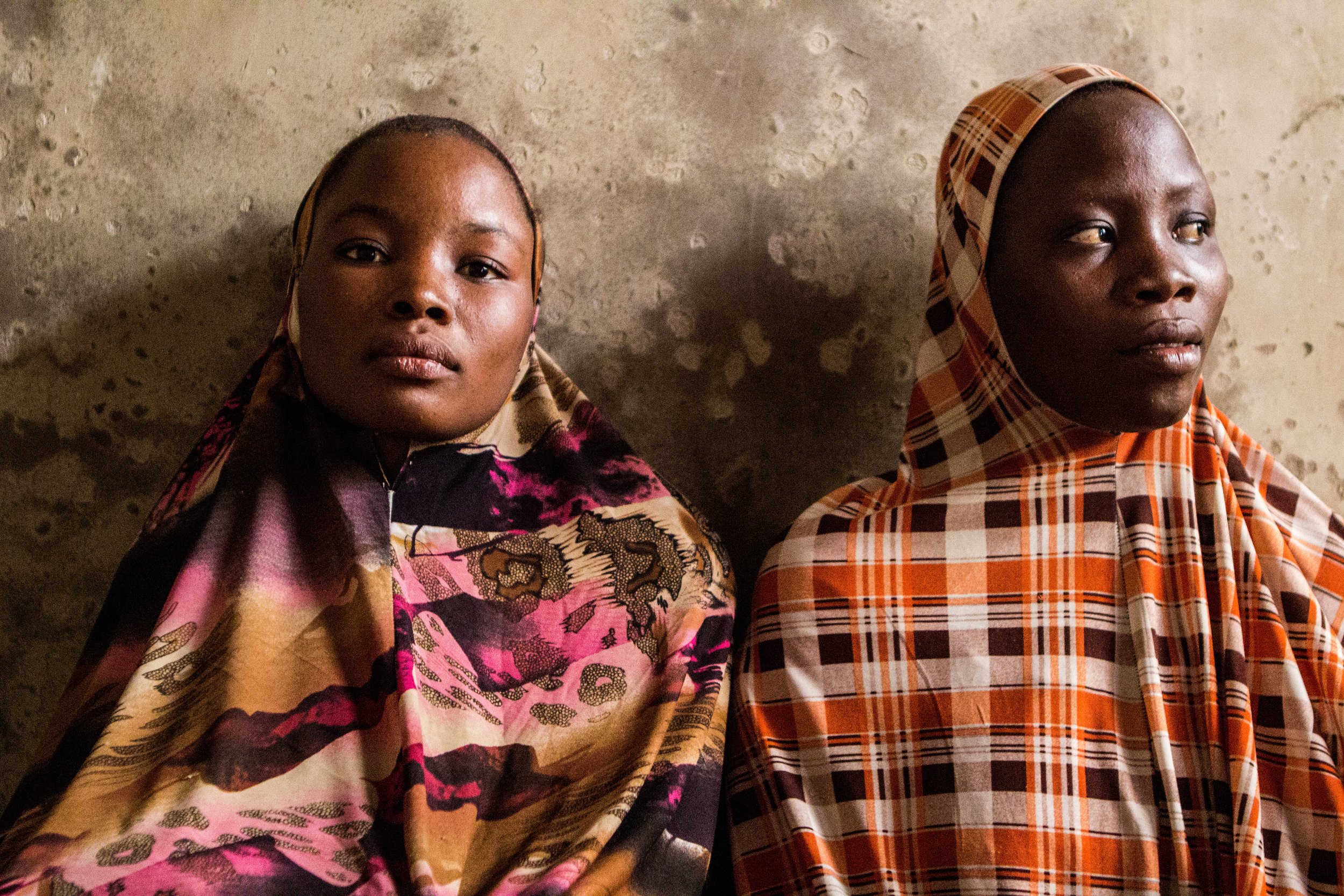 """Yola, Nigeria. March 7 2015. Hadiza Ibrahim, 22 and Rukayya, 20 stayed in their hometown after Boko Haram militants attacked and their husband fled for his life.  """"They both wanted to marry me,"""" Hadiza said. """"They said that, since he left, I was part of their property."""""""