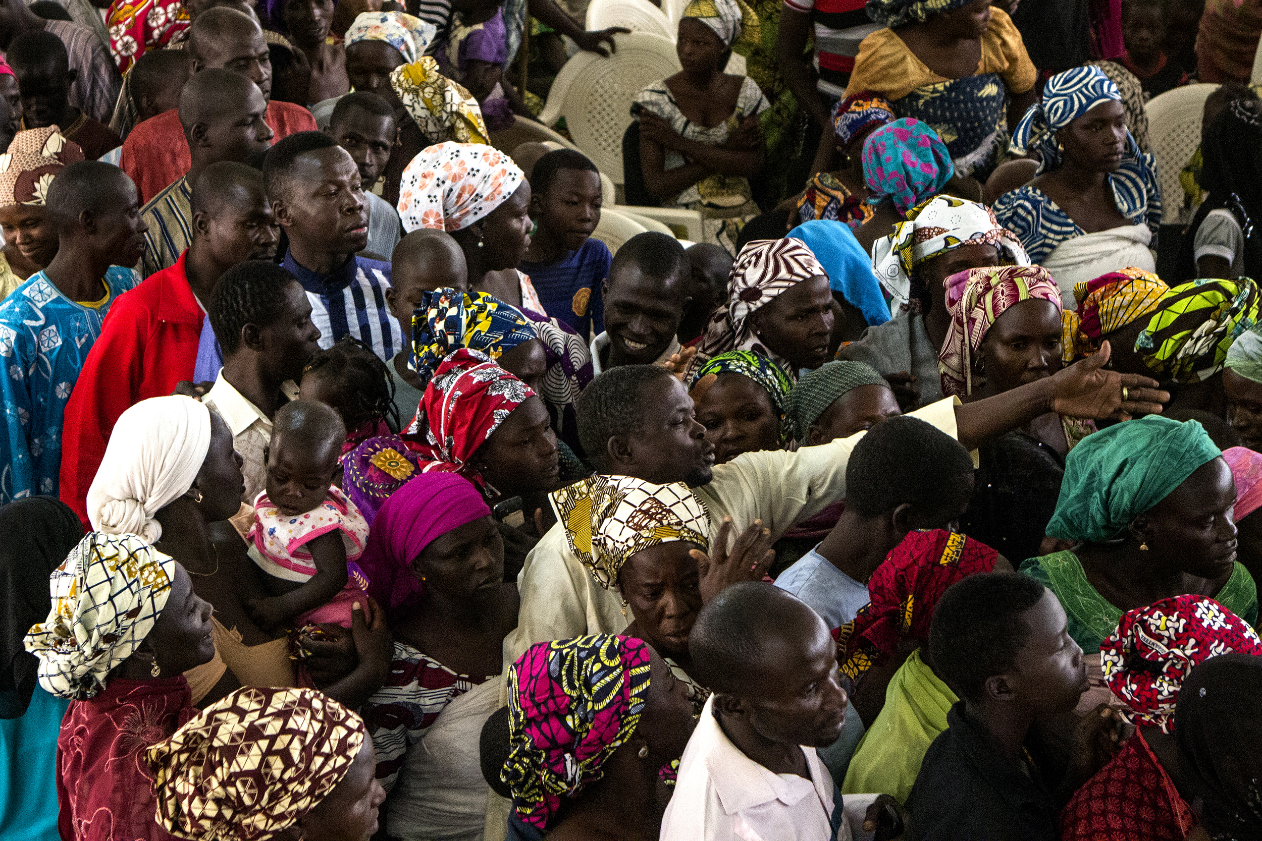 A man tries to organize a group if internally displaced persons waiting for a food at a church in Yola, Nigeria, March 1, 2015.