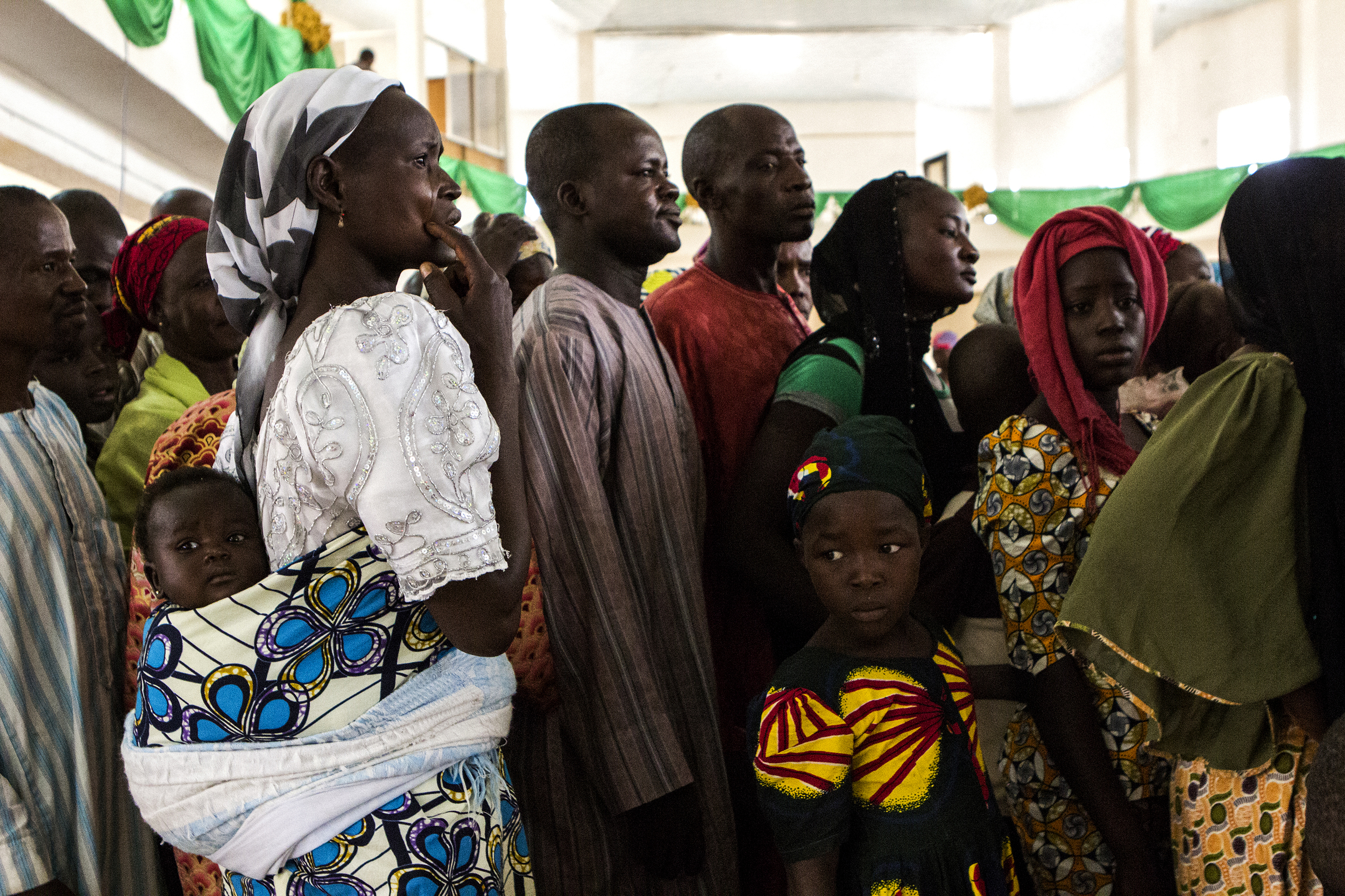 Yola, Nigeria. March 1 2015. Internally displaced people (IDPs) who have fled Boko Haram territory wait in line at a food distribution at a local church. Sometimes the process can take hours.