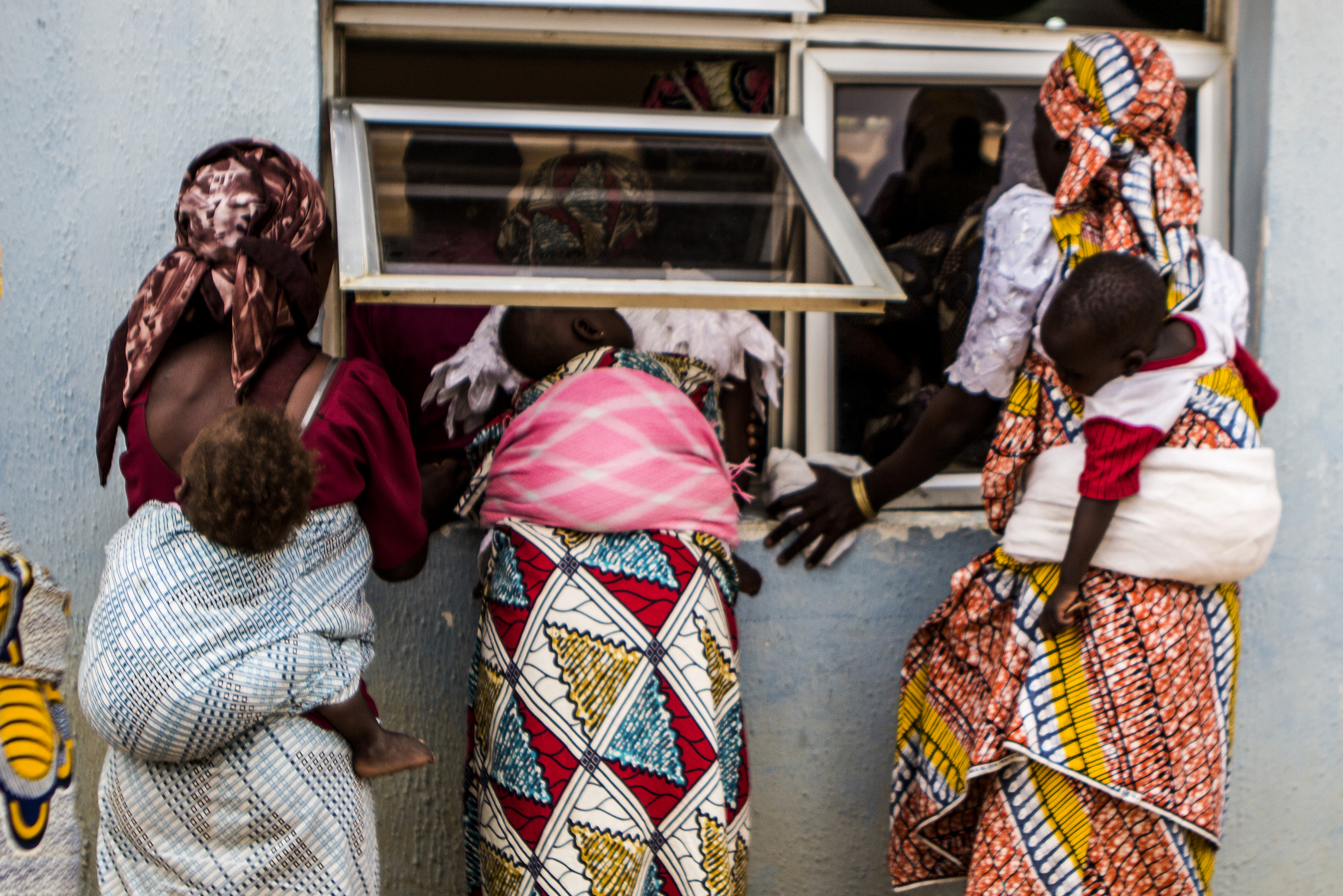 Yola, Nigeria. March 1 2015. Three women who have fled Boko Haram violence look through a window at a local church as aid groups distribute food donations. Many woman fled the militant's attacks while pregnant, and now are taking care of their small children whilst living in informal camps or with relatives.