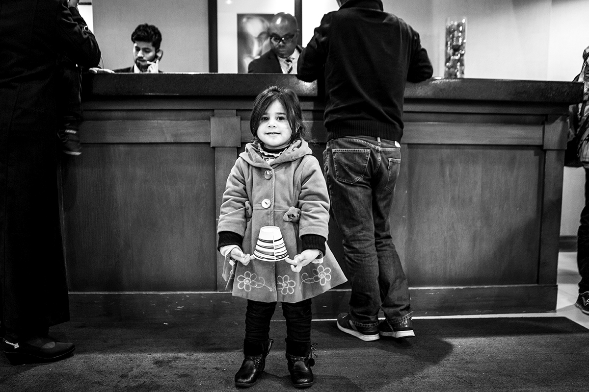 A young Syrian girl waits in a hotel lobby in Toronto where organizers are connecting recently-arrived Syrian refugees with their families or sponsors in Canada. The Canadian government resettled more than 10,000 Syrian refugees in the last months of 2015, many of whom were  sponsored by private groups who worked to raise enough money and resources to help the new arrivals settle into their communities. Dec. 21, 2015. Toronto, Ontario. | Kathleen Caulderwood