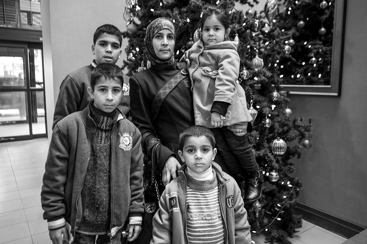 A mother gathered her children for a portrait near a Christmas tree on Dec. 21, 2015 in Toronto, Ontario. | Kathleen Caulderwood