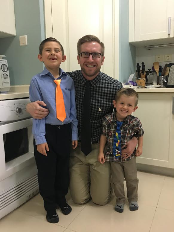 "Ryan pictured with his two sons. "" They both wore their ties and dress pins to school with me as a sign of their support for Dressember. We encouraged our oldest son, Gavin, to share with others that he is wearing a tie and a pin to raise funds to help those around the world in need. He's in Kindergarten. We haven't broached the subject of slavery with him yet."