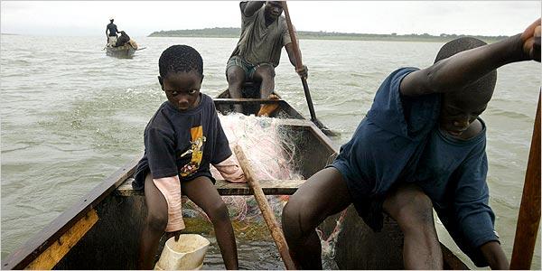 On Lake Volta in Ghana, Mark Kwadwo, 6, left, scoops water in the canoe of Kwadwo Takyi, rear. Kwabena Botwe, 11, paddles. Photo Credit: Joao Silva for The New York Times