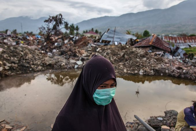 PHOTO: A survivor, Tina, standing in a damaged area waits for news of her daughters, Marsha and Keila, as they search for victims following the earthquake on Oct. 11, 2018 in Palu, Indonesia. The death toll climbed past 2,045 and officials warn another 5,000 people remain missing and feared buried in mud and rubble. Ulet Ifansasti, Getty Images