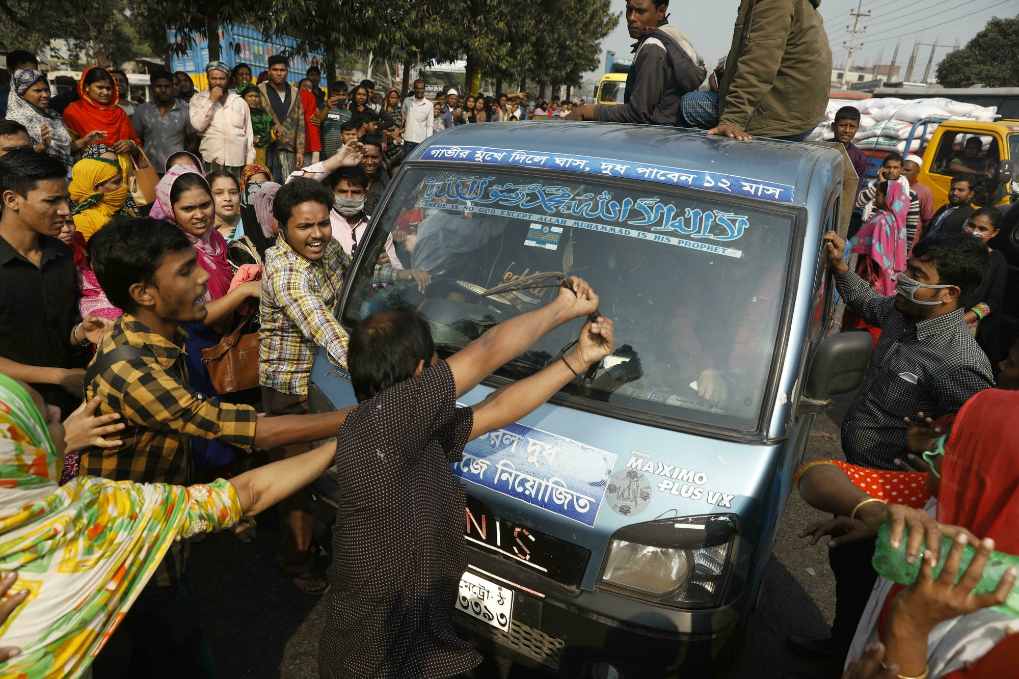 In this Wednesday, Jan. 9, 2019 file photo, Bangladeshi garment workers vandalize a vehicle during a protest in Savar, on the outskirts of Dhaka, Bangladesh. Kalpona Akter of the Bangladesh Center for Worker Solidarity said Thursday, Jan. 31, that more than 5,000 garment workers demanding wage hikes have been laid off while hundreds of them are facing police charges in the world's second-largest garment export industry. She said the firings came after thousands of workers took to the streets earlier this month in and around Dhaka, the nation's capital. (AP Photo)