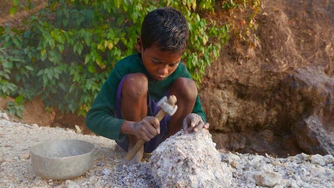 Six-year-old Shamil Murmu breaks rocks to fill his bowl with the prized mineral.  Credit: ITV News/Sean Swan