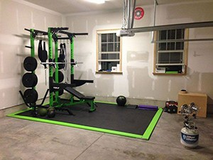 Simple-and-clean-heated-garage-gym-with-green-weight-bench-set-wall-balls-and-yoga-mats.jpg