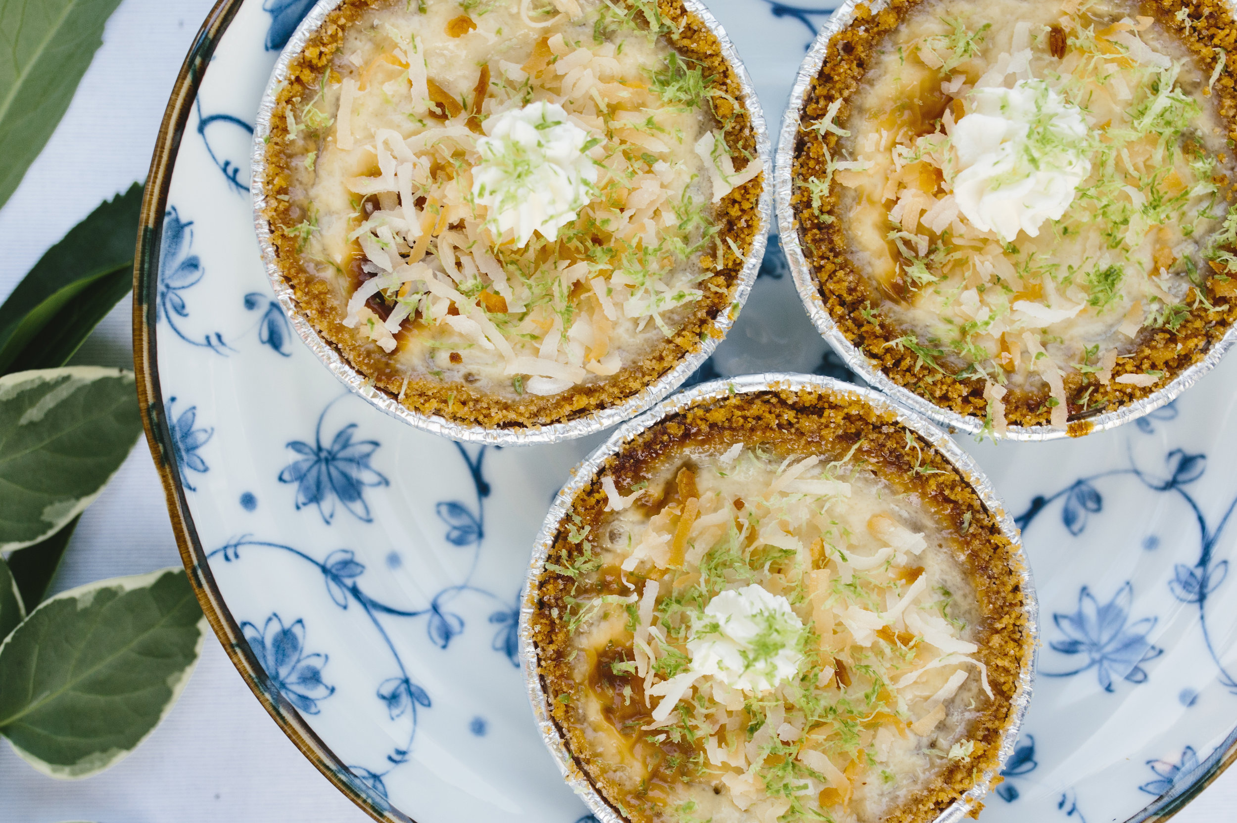 The Coconut Key Lime pies topped with handmade whipped cream, lime zest, and some toasted coconut shreds.