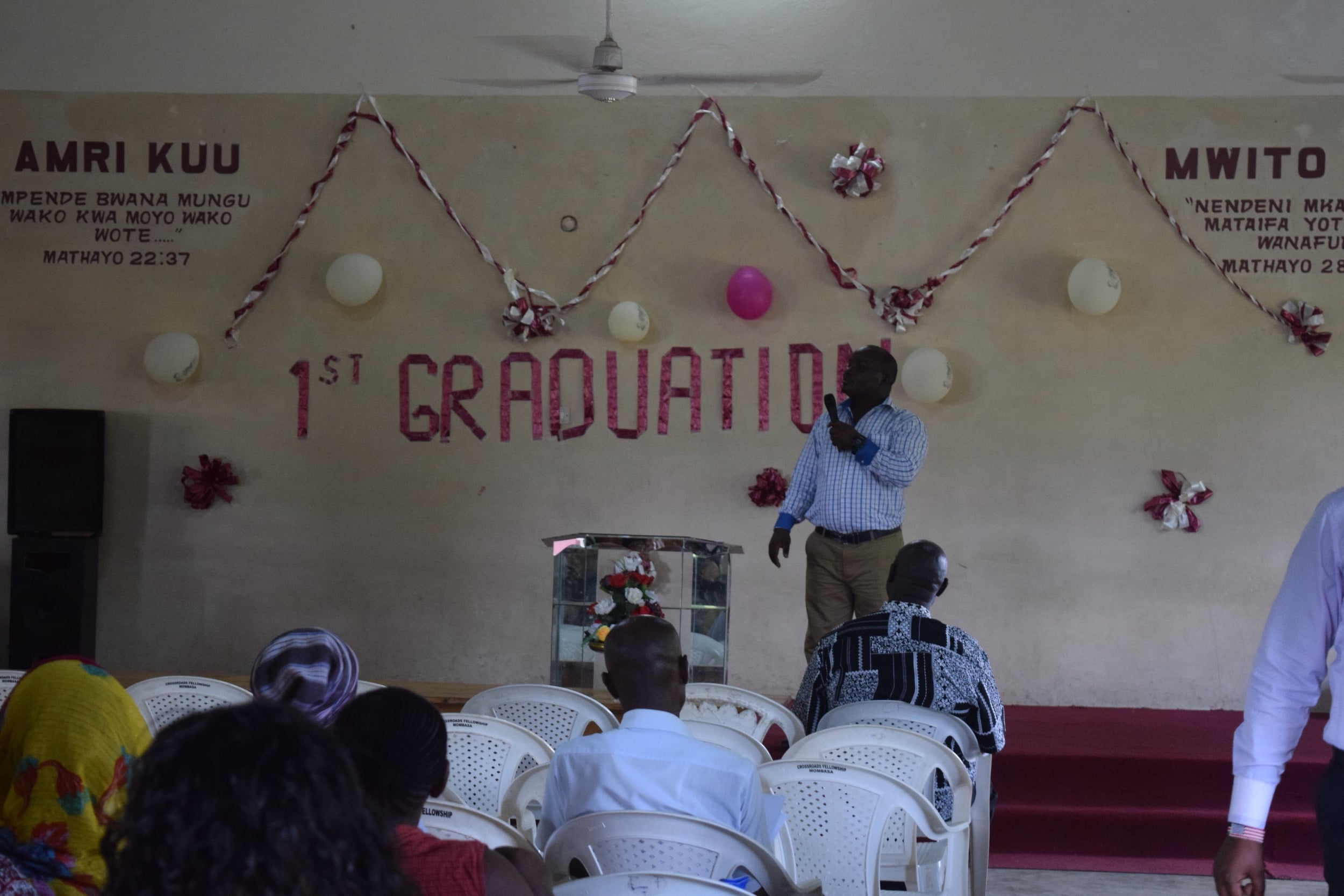 Teacher James speaking to the graduates, the teachers, and the families