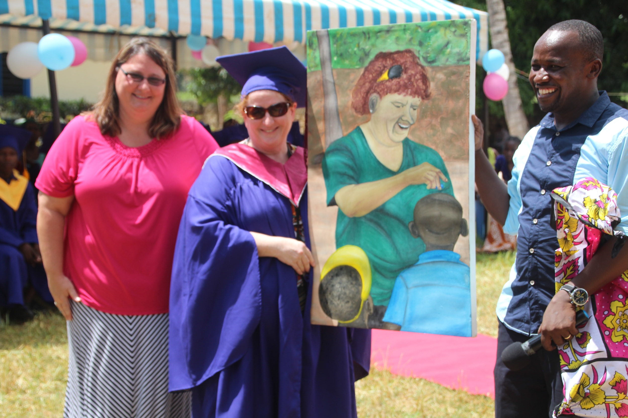 Lisa Becthel and Pastor Allan pose with Denise holding the portrait of her and the students in Bomani.