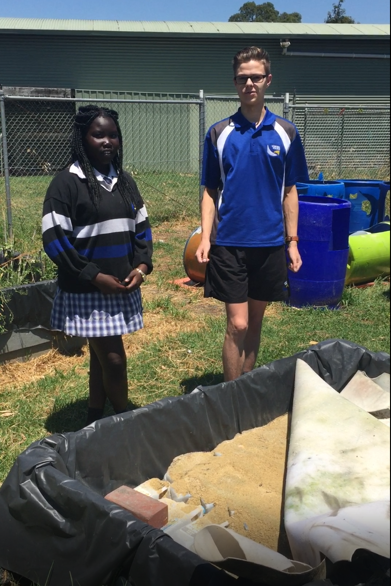 Nyachou Gawar and Trent Euman in front of a Wicking Garden under construction