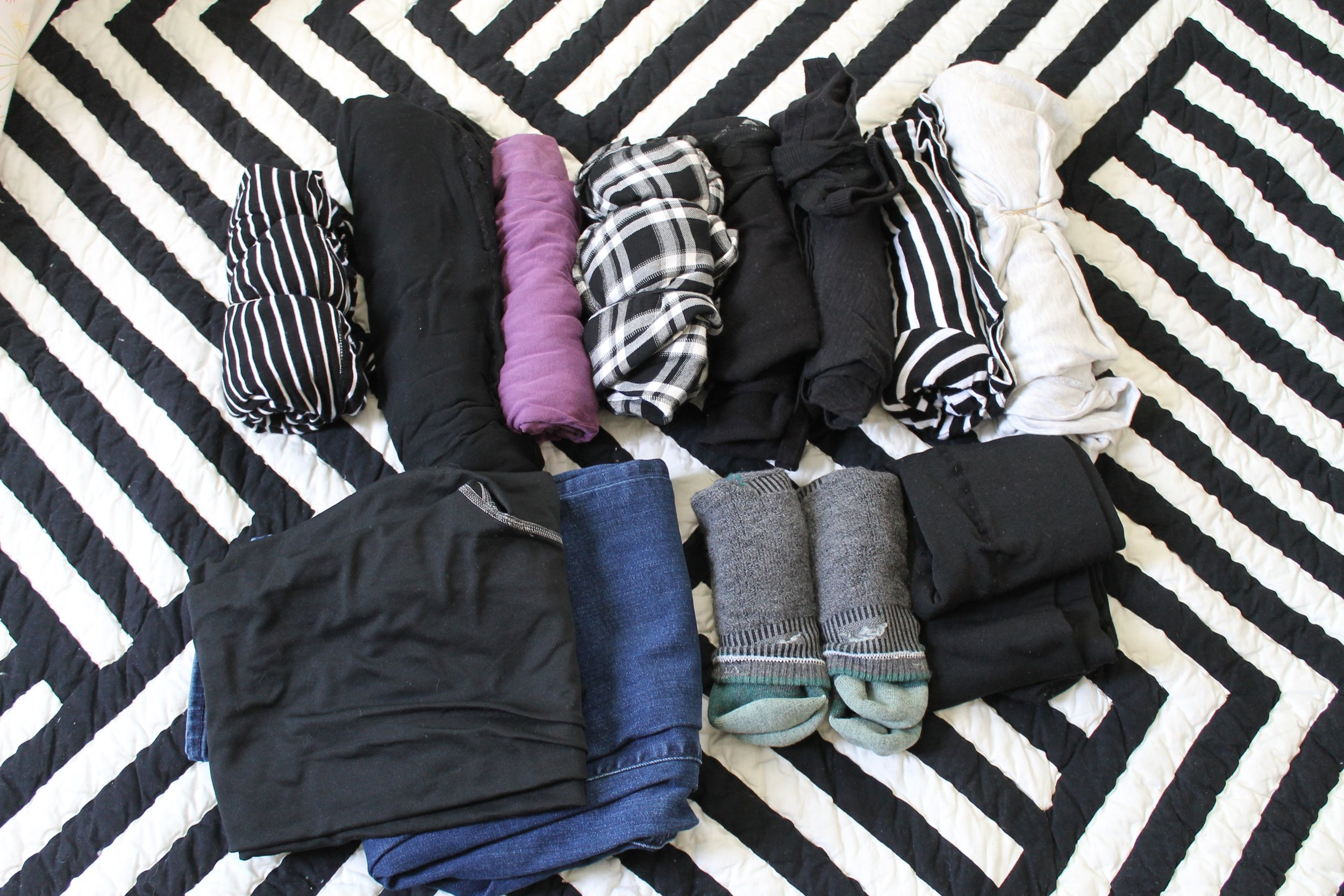 L-R: T-shirt dress, pj pants, pj shirt, long sleeved flannel, black sweater, black t-shirt, black and white striped long sleeve shirt, short sleeve shirt. Leggings, jeans, two pairs of socks, tights. Not pictured in this is the outfit I'll be wearing on the plane
