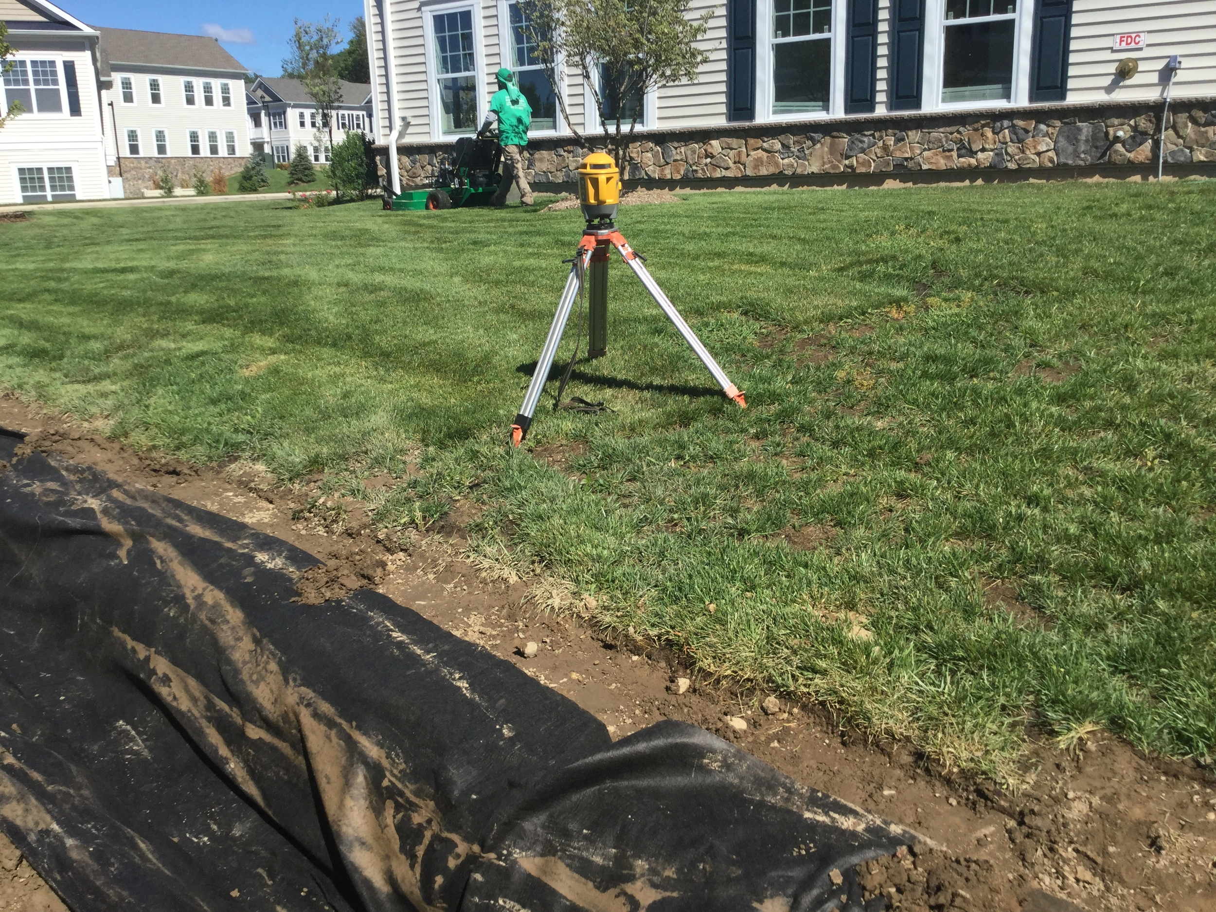 Survey equipment is used in the construction process to ensure quality and the highest level of craftsmanship. Grasskeepers Landscaping Inc. One of our landscape maintenance professionals is shown keeping up with the grounds in the background.