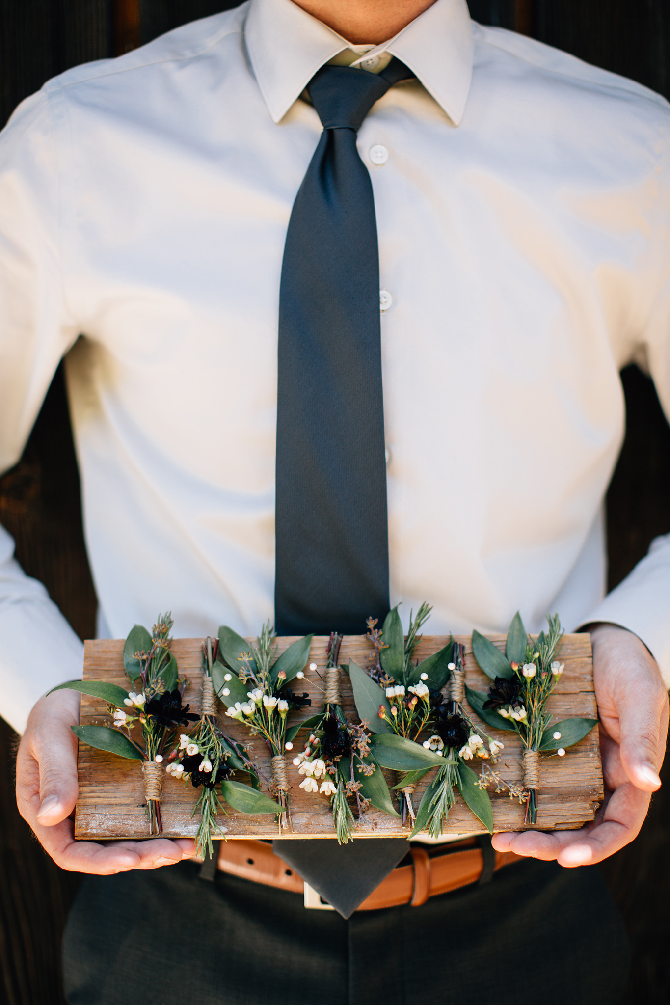 groom hodling boutonnieres