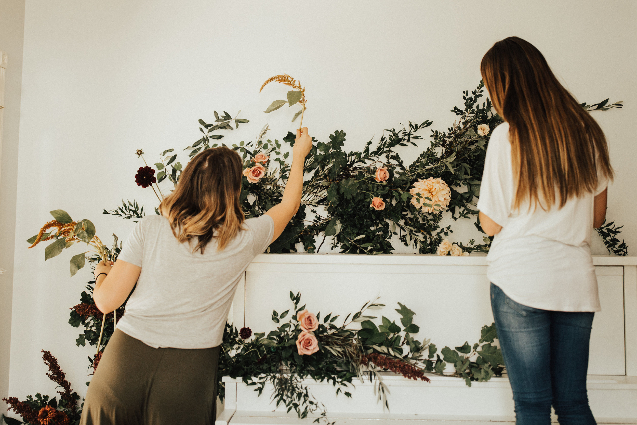 placing flowers in the greenery