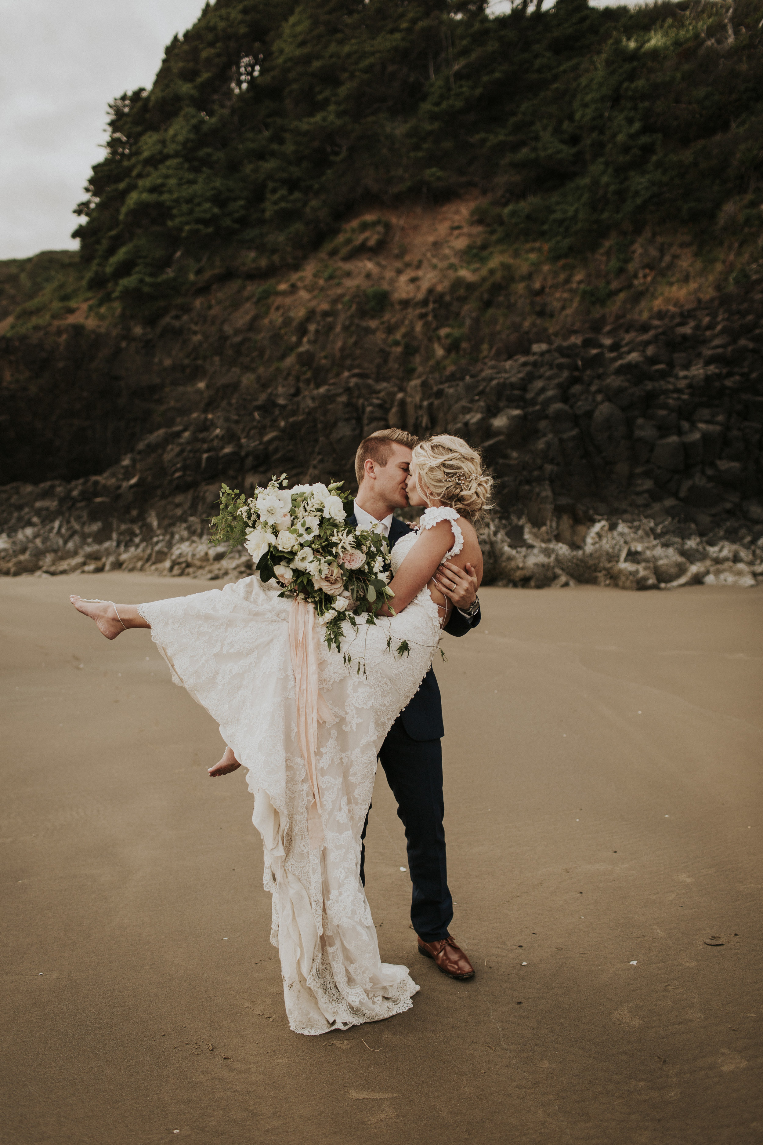 newlyweds with flowers on the oregon beach