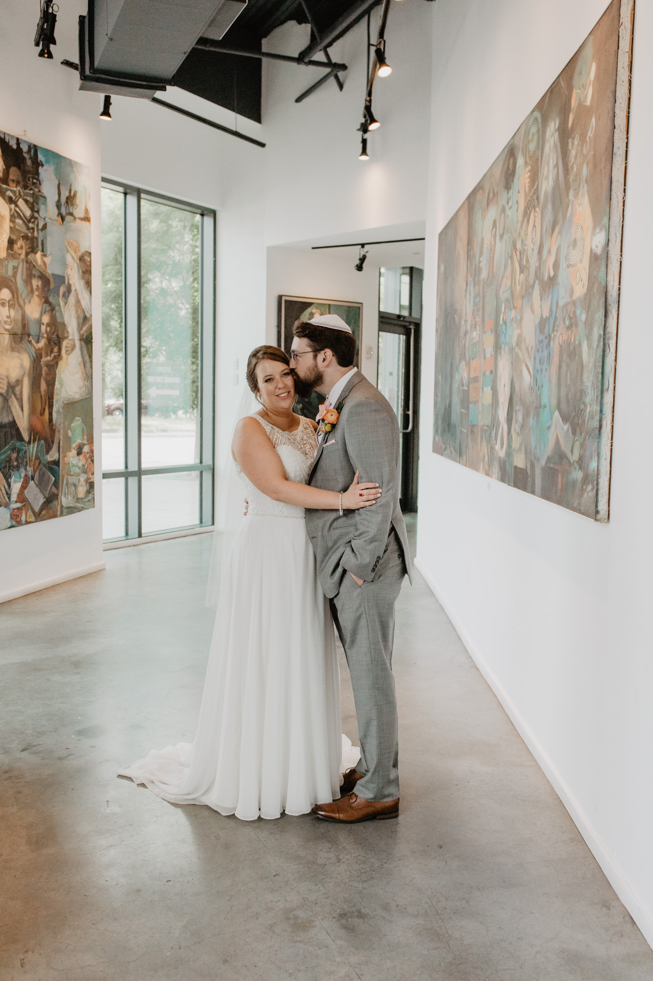 Bride and groom pose in the gallery space of Boston City Winery