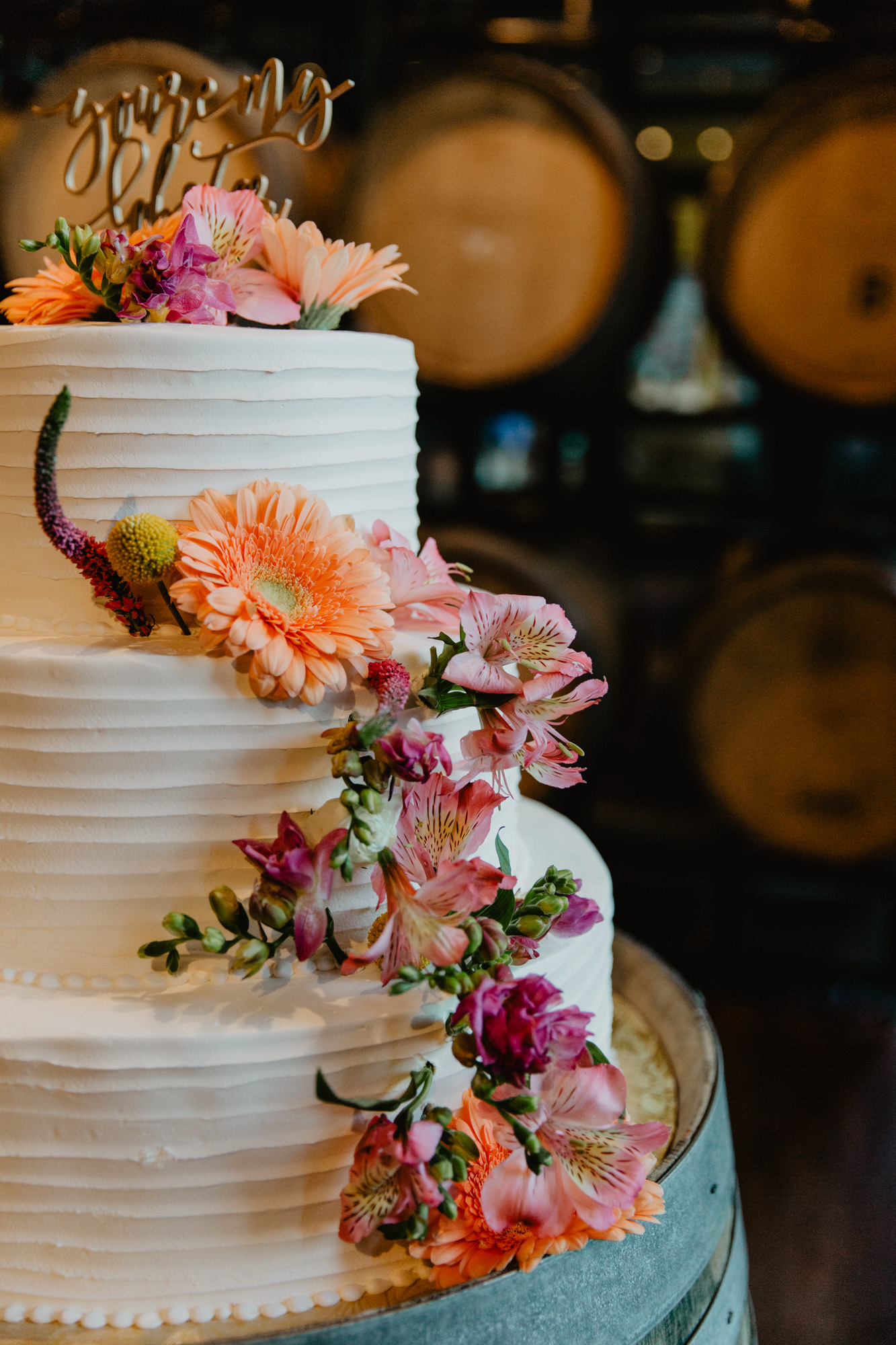 Colorful orange and pink florals on a wedding cake designed by Konditor Meister