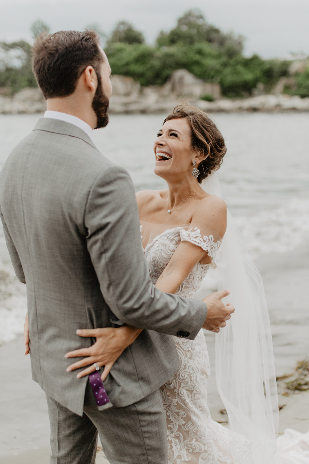 Bride embraces groom by the shore at the Portland Head Lighthouse