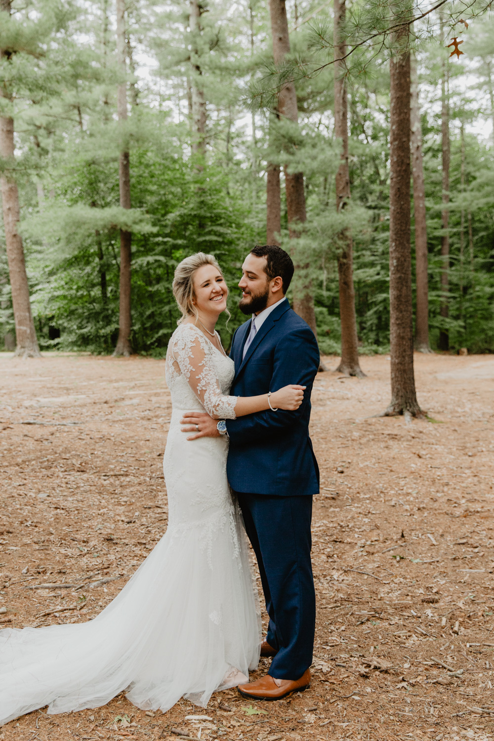 Bride and groom pose in the woods at Camp Wing, Duxbury