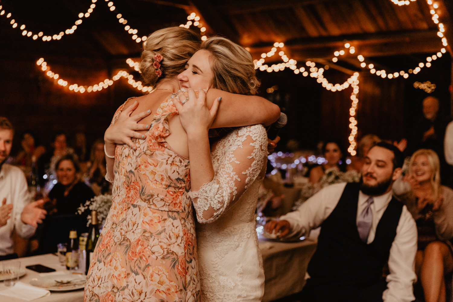 The bride hugs her sister at her Camp Wing summer camp wedding