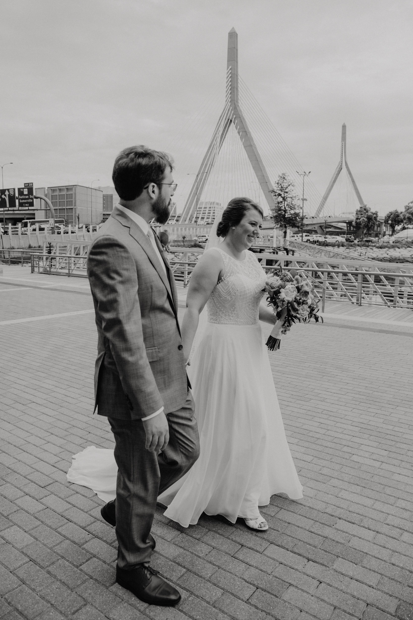Bride and groom walk hand in hand at Lovejoy Wharf in Boston with the Zakim Bridge in the background