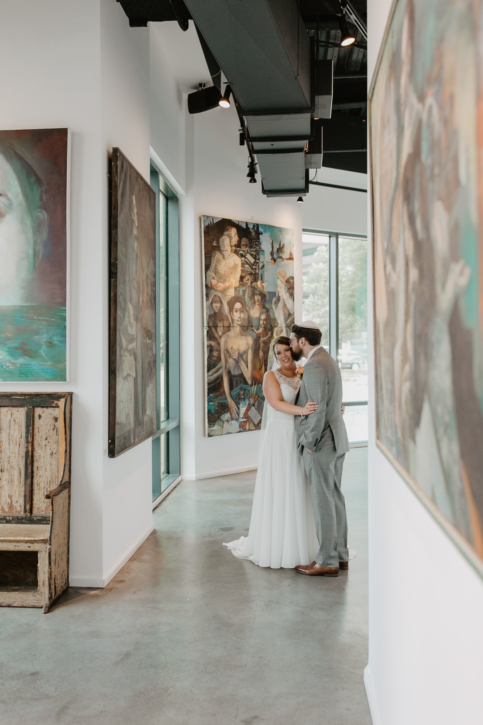 Bride and groom pose in the City Winery Boston art gallery