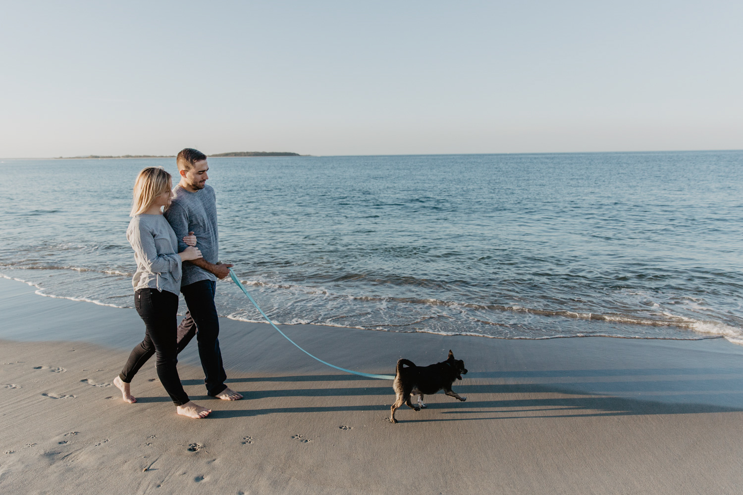 A couple and their dog walk along Cranes Beach during their engagement session