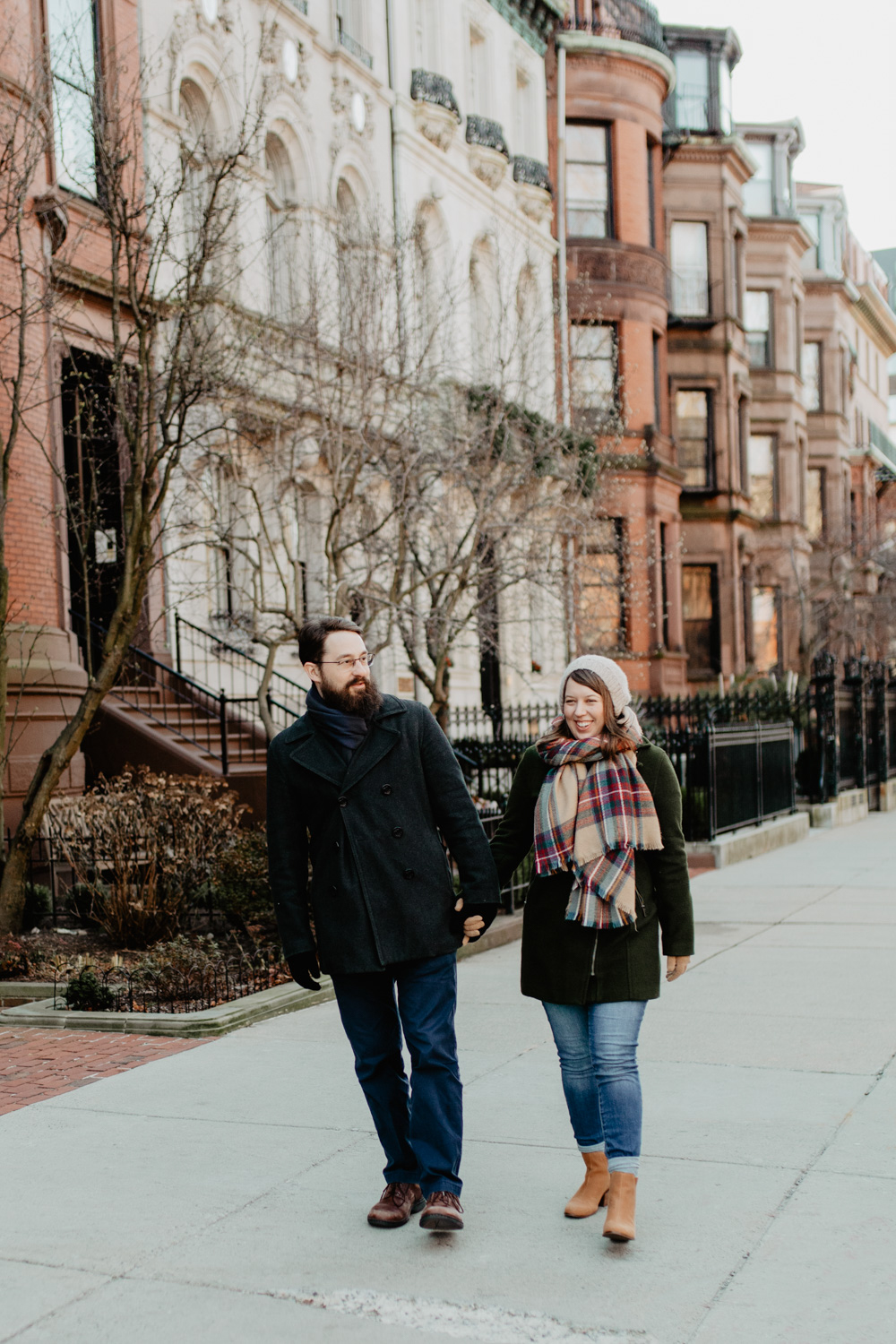 A couple walks down a Boston street during their winter engagement photos