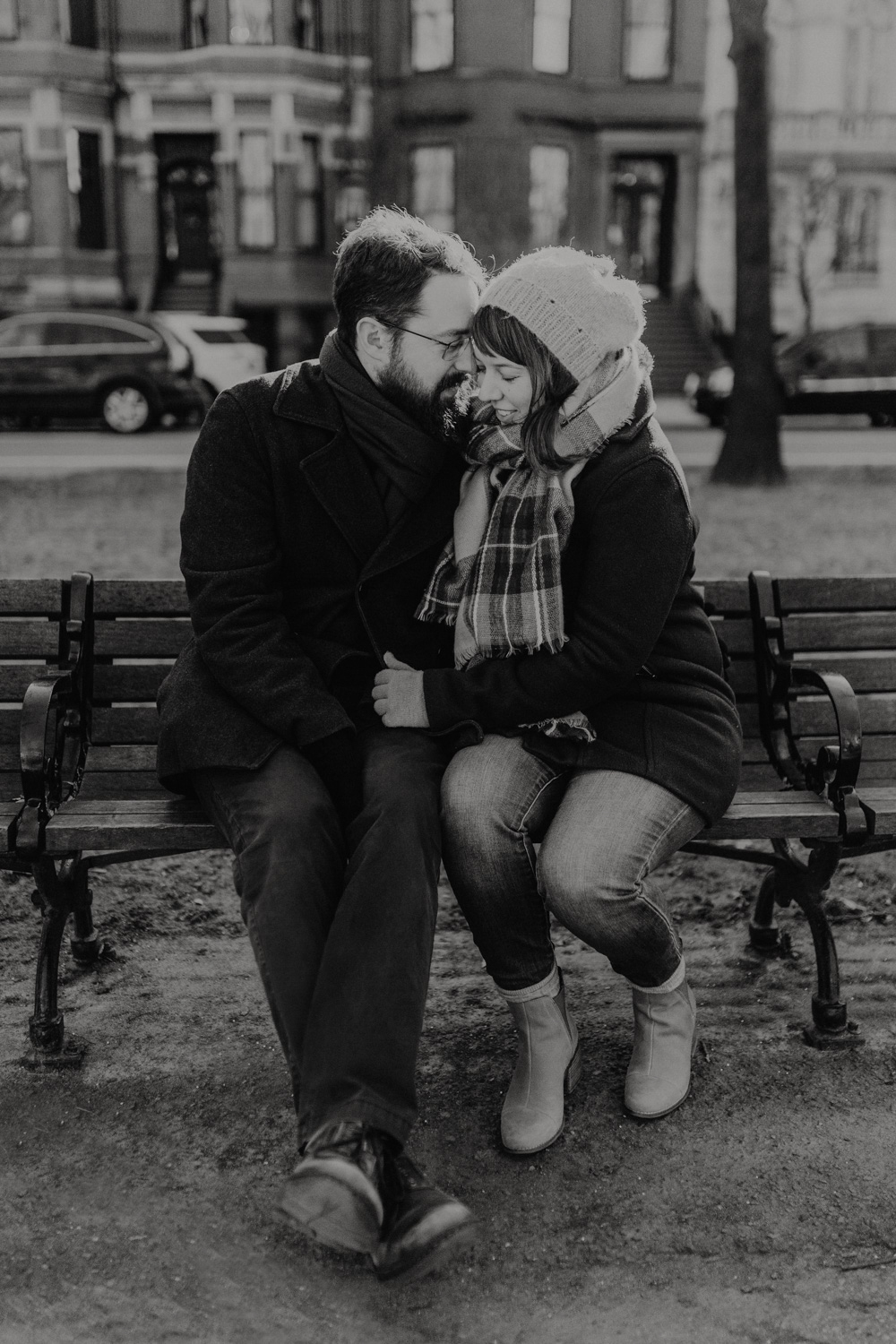Winter engagement photo on a bench in Boston MA