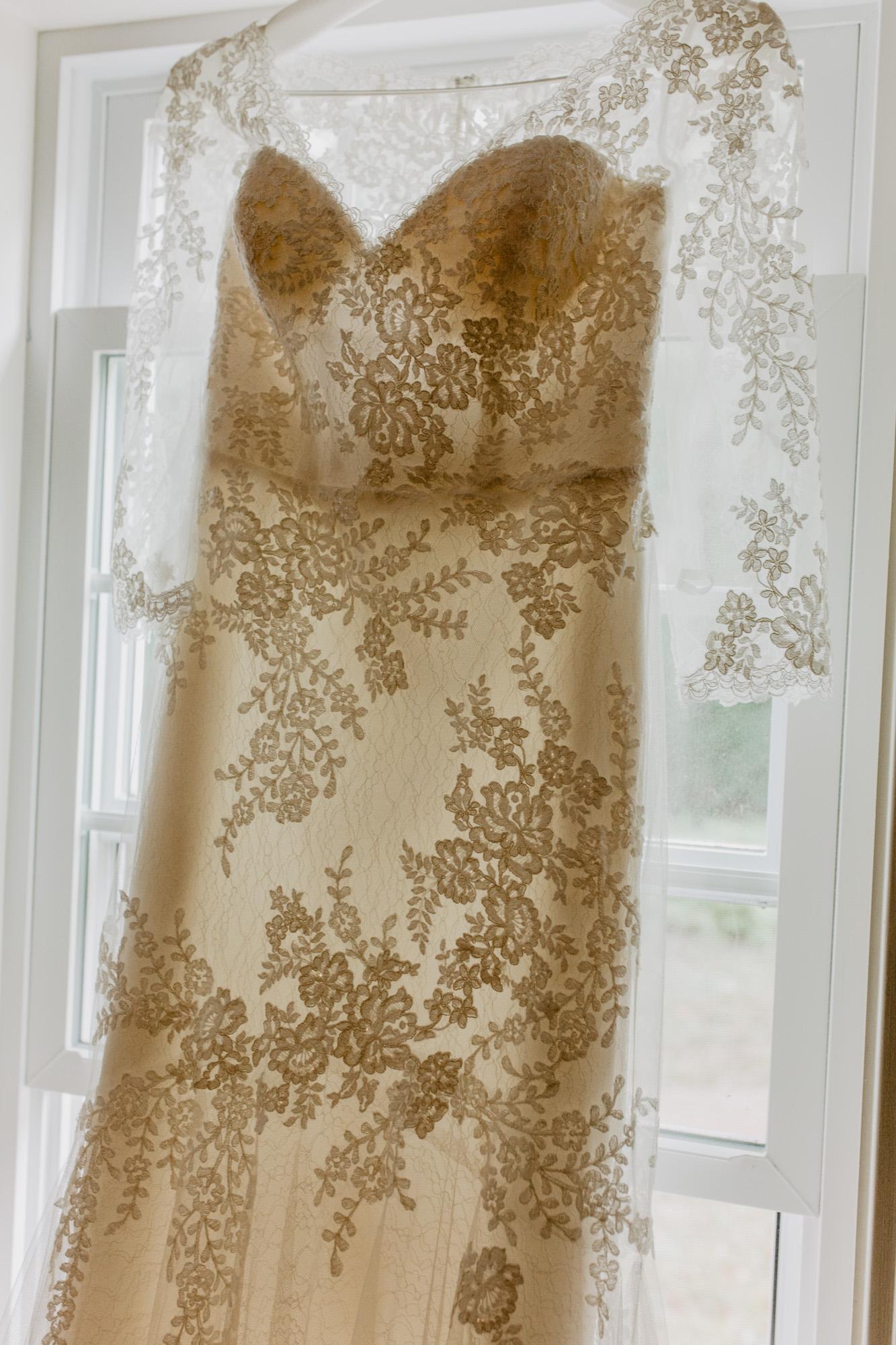 The bride's lacy wedding dress hangs by a window