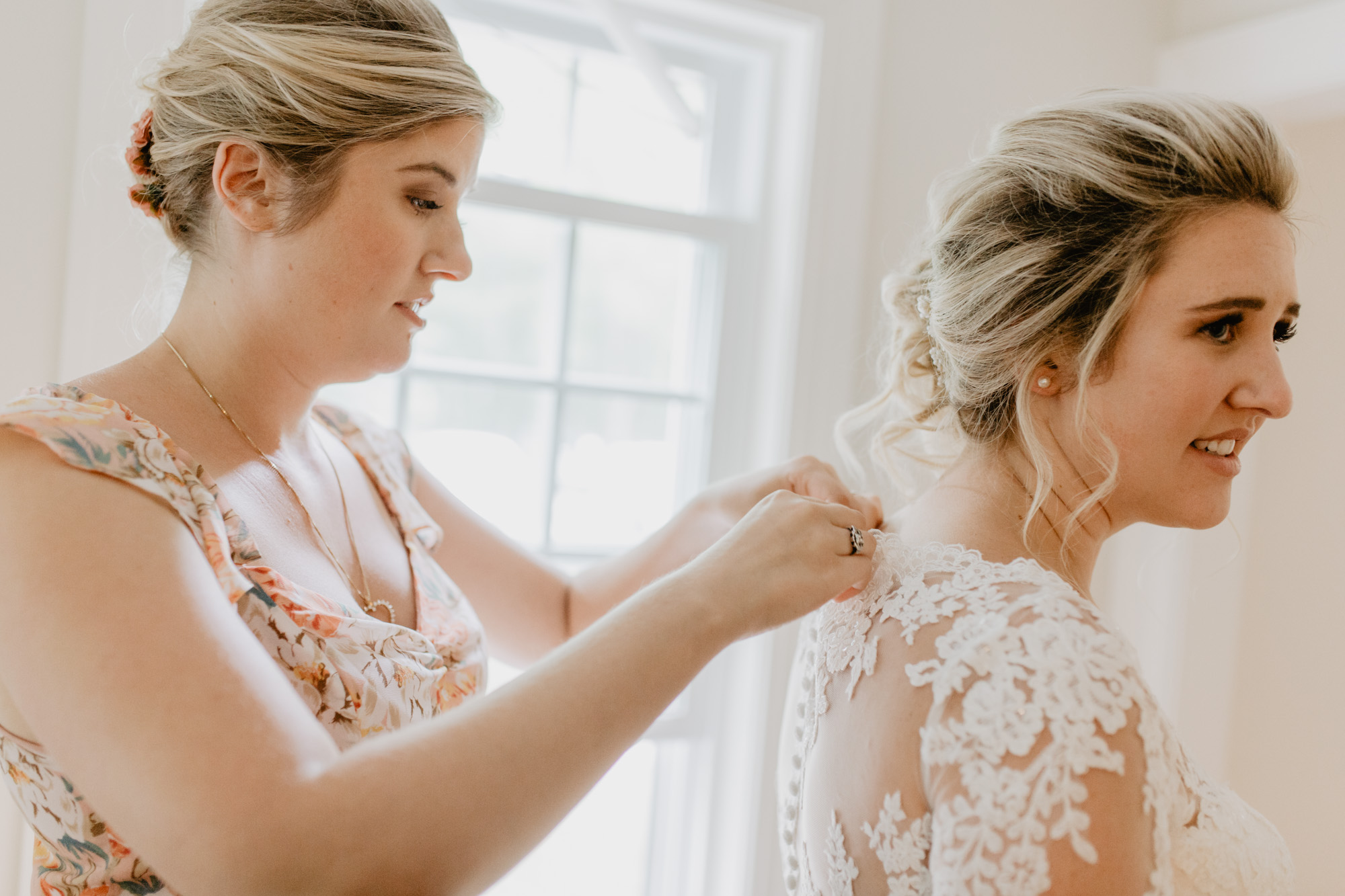 The bride buttons up her wedding dress