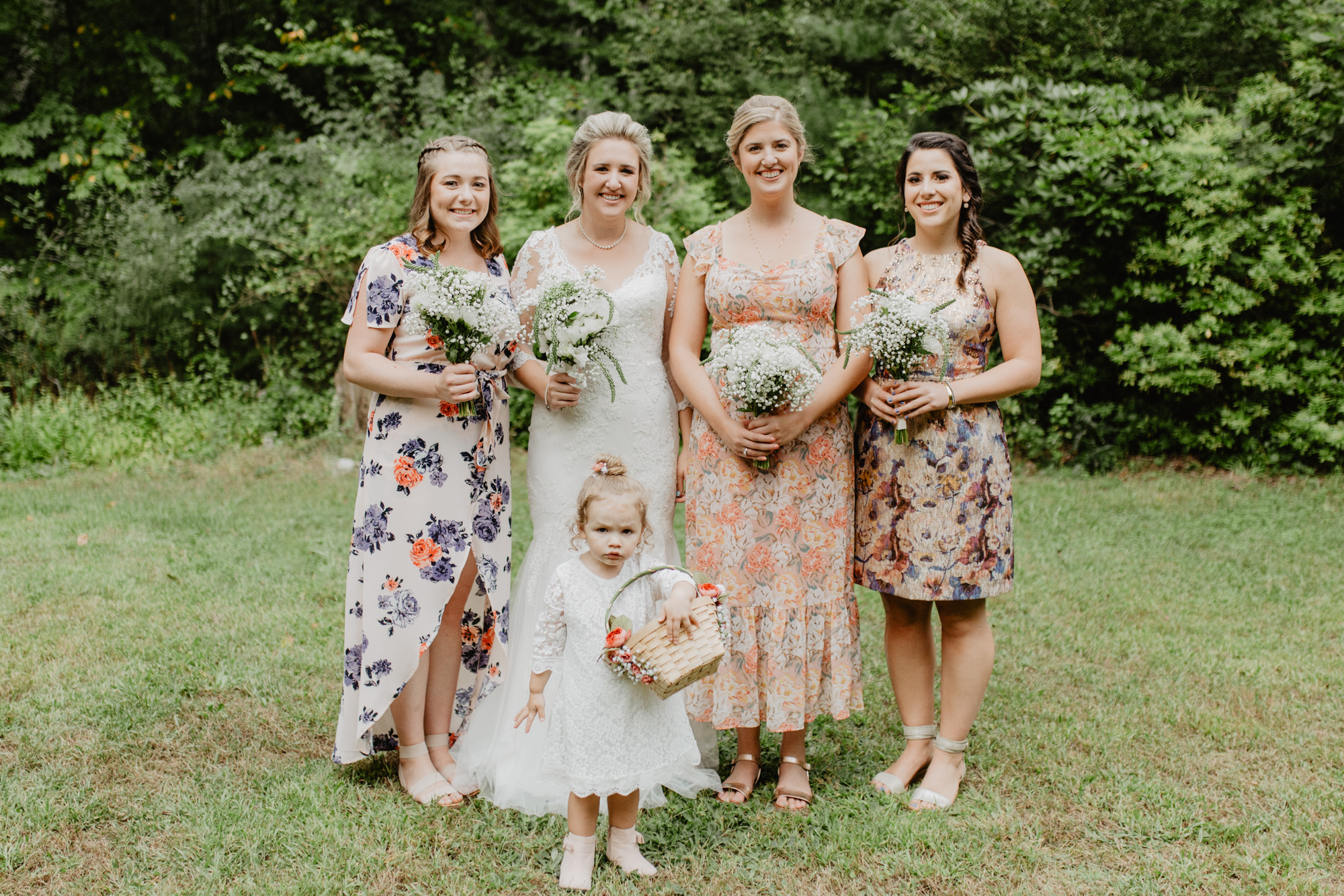 The bride and her bridesmaids dressed in floral dresses