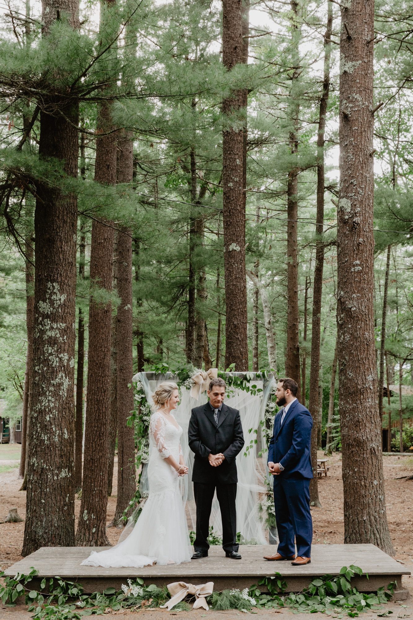 The couple says their vows at their wedding in the woods