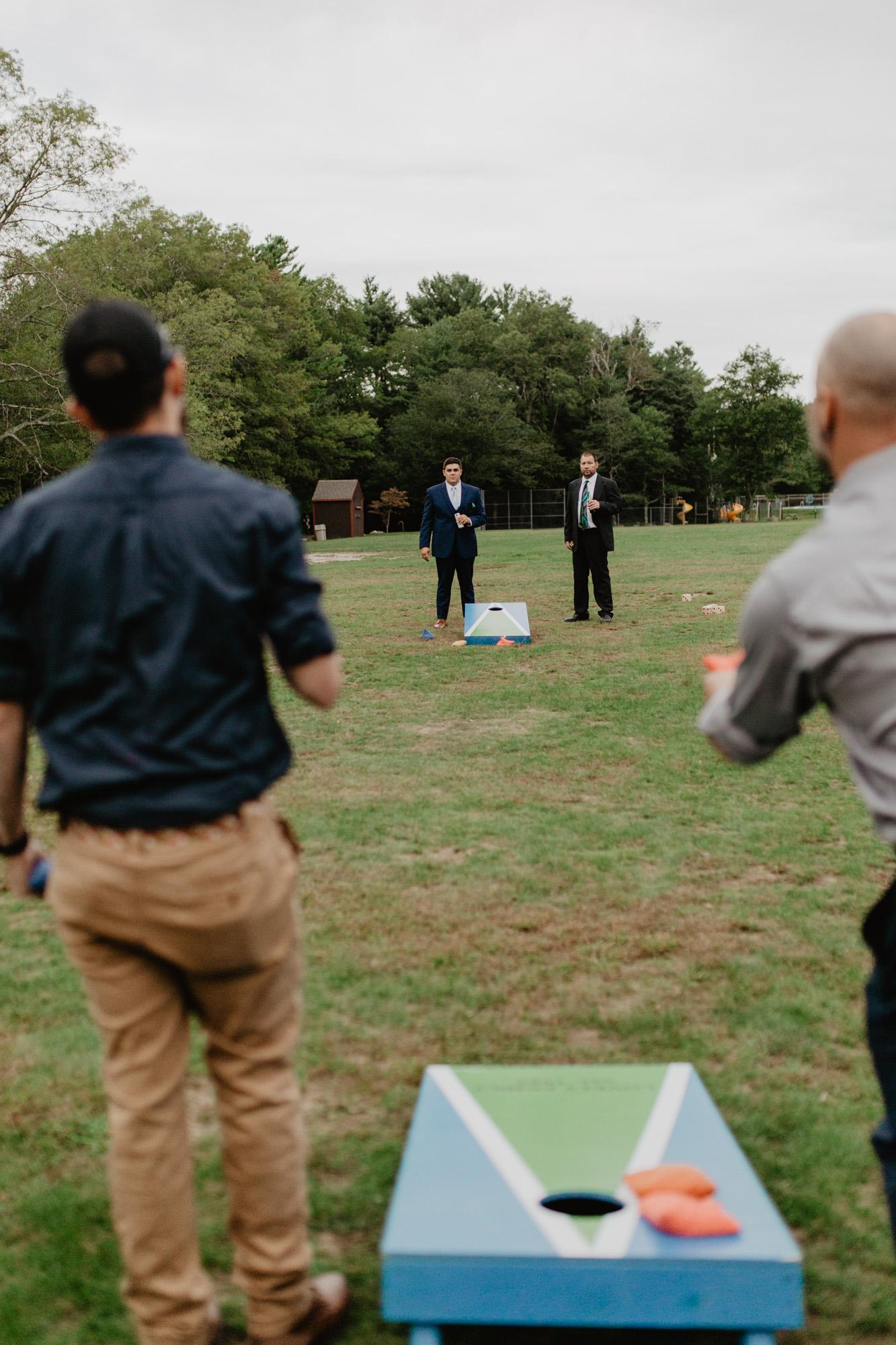 Guests play cornhole at Camp Wing wedding