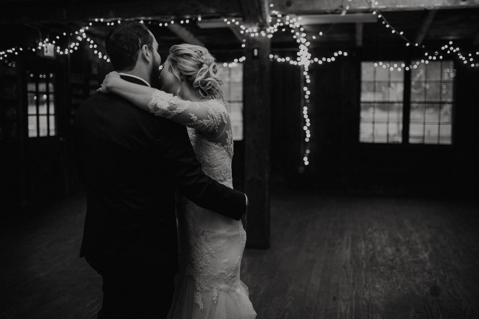 The bride and groom have their first dance beneath fairy lights in the camp's mess hall