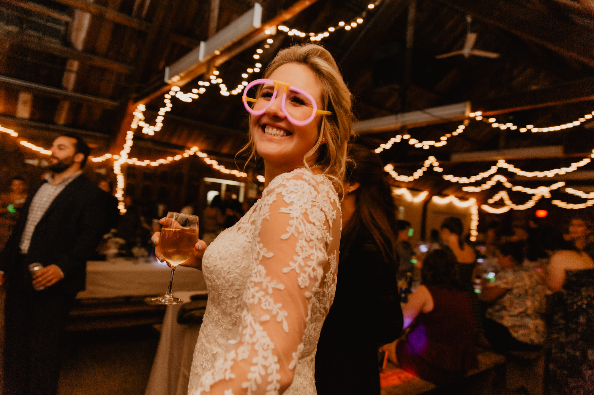 The bride poses while wearing a pair of glow stick sunglasses