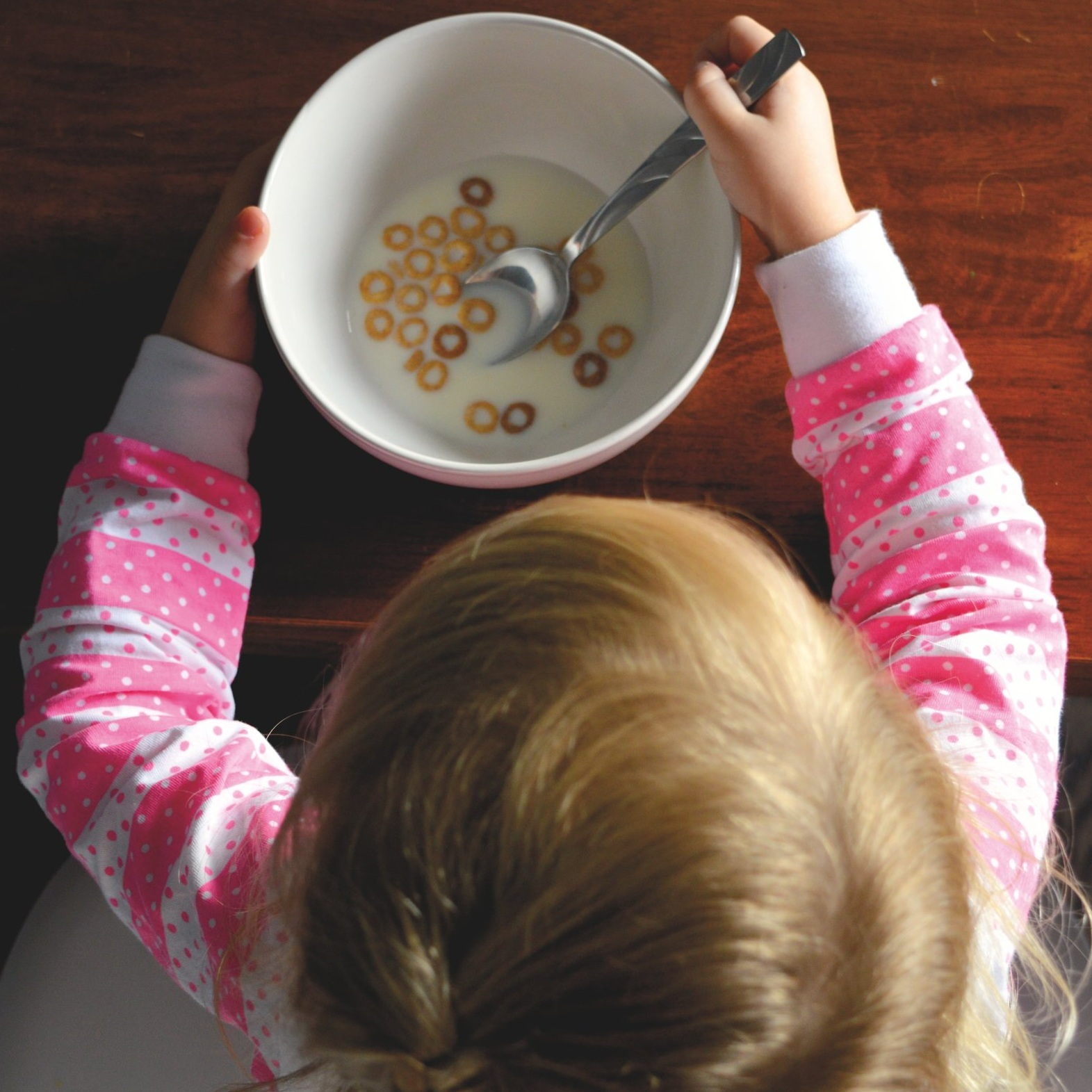 A little girl in pink and white pajamas looks at her nearly empty cereal bowl.