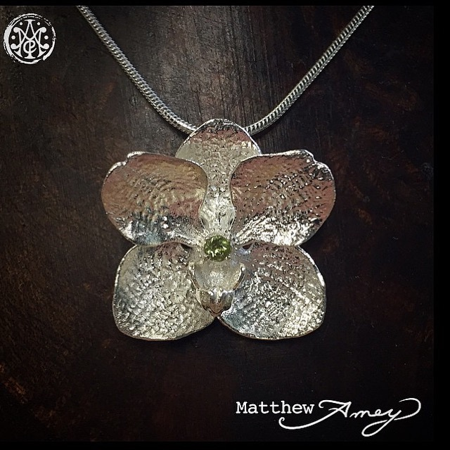 Orchid pendant in sterling silver, set with a peridot.