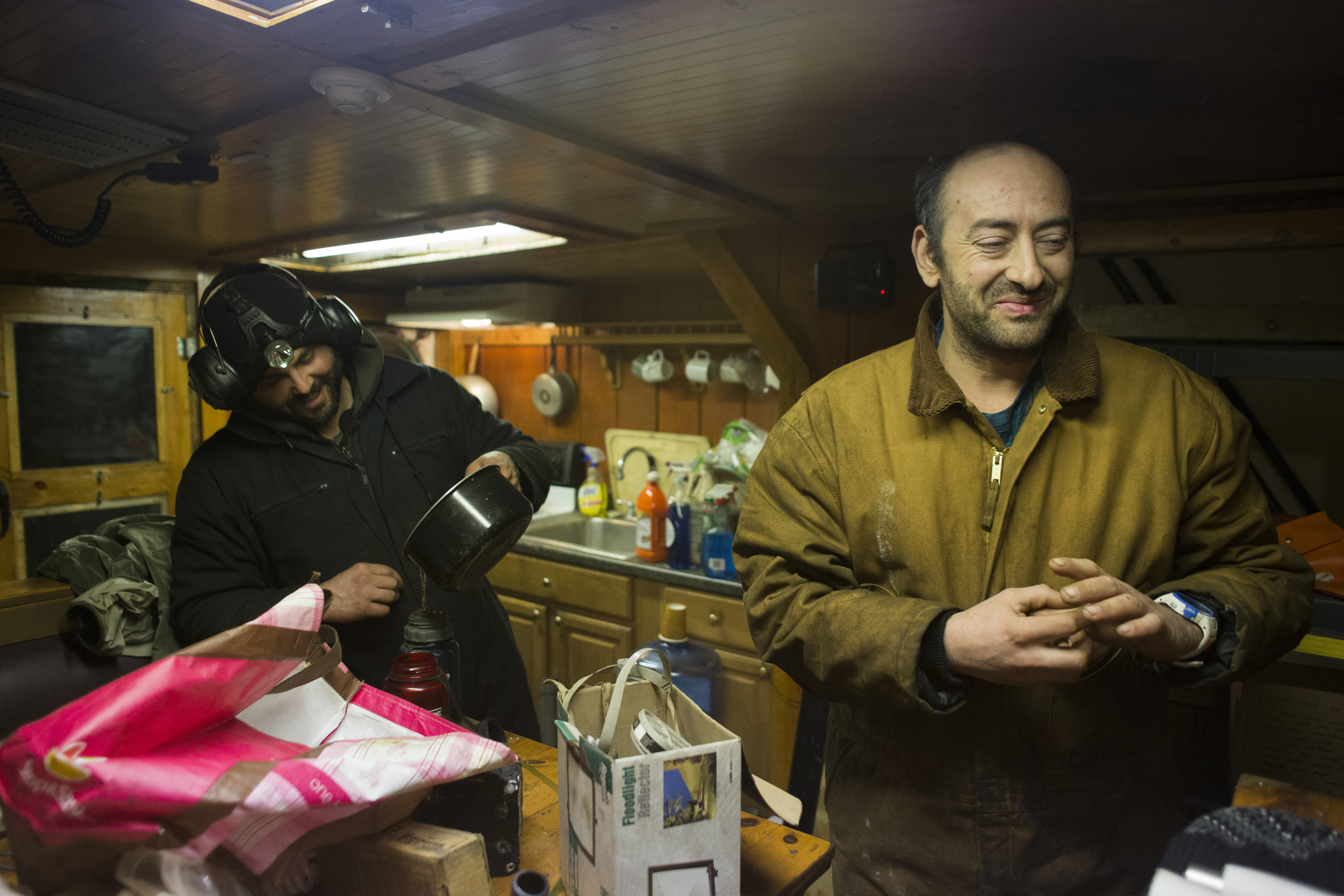 Chris and Mike laugh while making peanut butter and jelly sandwiches, fast calories to keep themselves awake, in the  Oxman 's galley.